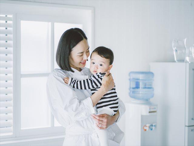 ウォーターサーバーは赤ちゃんのいるご家庭必見!-赤ちゃんの成長には水が欠かせない。ウォーターサーバーの水は不純物をしっかりと取り除いた水だけを提供しているため、赤ちゃんにも安心-クリクラを背景にウォーターサーバーの水は軟水なので安心だと表現している親子の画像